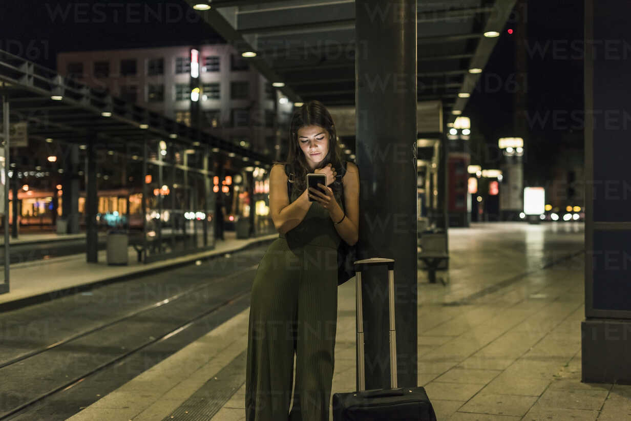 Young woman waiting at the station by night using cell phone - UUF11072 - Uwe Umstätter/Westend61