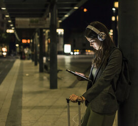 Young woman with headphones and tablet waiting at the station by night - UUF11075