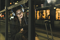 Portrait of young woman with headphones waiting at the station by night using tablet - UUF11078