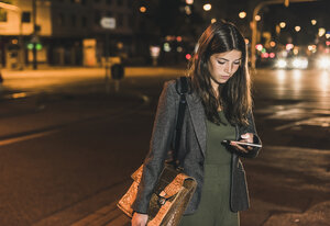 Young businesswoman with leather bag looking at cell phone by night - UUF11081