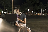 Young woman with smoothie sitting on bench at night  using laptop - UUF11087