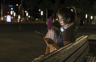Young woman with smoothie sitting on bench at night using tablet - UUF11090