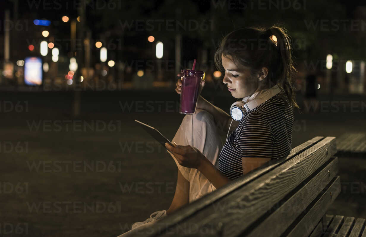 Young woman with smoothie sitting on bench at night using tablet - UUF11090 - Uwe Umstätter/Westend61