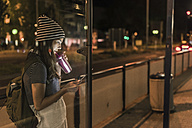 Young woman with smoothie waiting at station by night looking at cell phone - UUF11093
