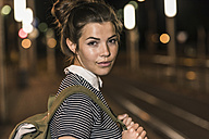 Portrait of young woman with backpack waiting at station by night - UUF11096