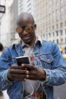 USA, New York City, Manhattan, portrait of man wearing mirrored sunglasses looking at cell phone - MAUF01167