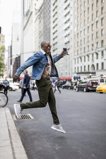 USA, New York City, Manhattan,  stylish man jumping in the air - MAUF01170