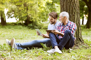 Senior father sitting besides his adult son in a park with tablet - HAPF01865
