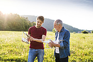 Senior father and his adult son with drone on a meadow - HAPF01868