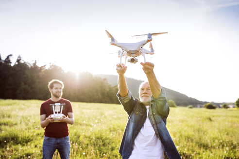 Senior father and his adult son with drone on a meadow - HAPF01871