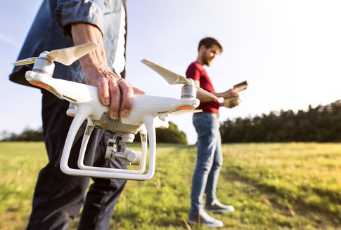 Senior father and his adult son with drone on a meadow - HAPF01874