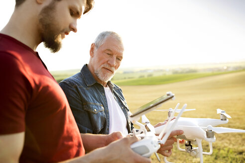 Senior father and his adult son with drone on a field - HAPF01877