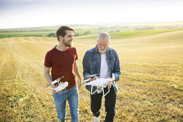 Senior father and his adult son with drone on a field - HAPF01880