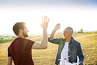 Senior father and his adult son with drone on a field - HAPF01883
