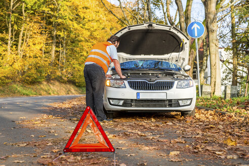 Man examining damaged car at roadside - PUF00658