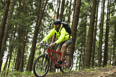 Man mountain biking in forest - MAEF12382