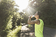 Jogger in the park drinking water - UUF11114