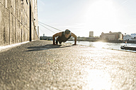 Fit athlete doing push ups at the river - UUF11141