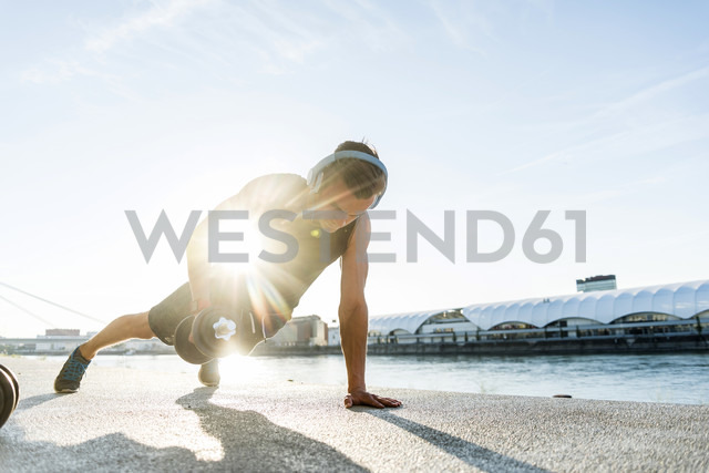 Fit athlete doing push ups at the river - UUF11147
