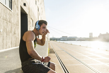 Young athlete wearing headphones, sitting on a wall - UUF11150