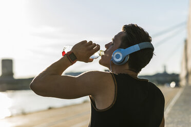 Young man wearing headphones, drinking water - UUF11153