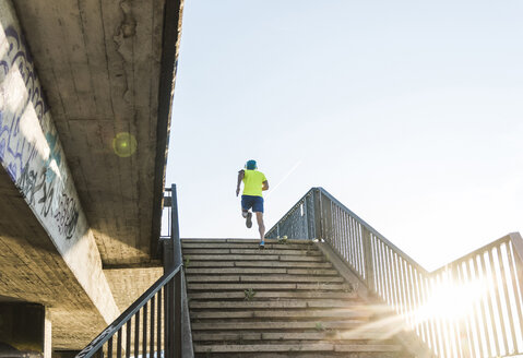 Young athlete jogging up stairs in the city - UUF11156