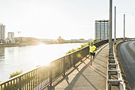 Young athlete jogging on a bridge in the city - UUF11159