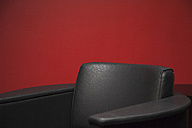 Black leather chair in front of red wall, partial view - JMF00401
