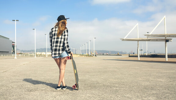 Back view of young woman with longboard standing in front of beach promenade, partial view - DAPF00767