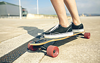 Feet of young woman on longboard, close-up - DAPF00770