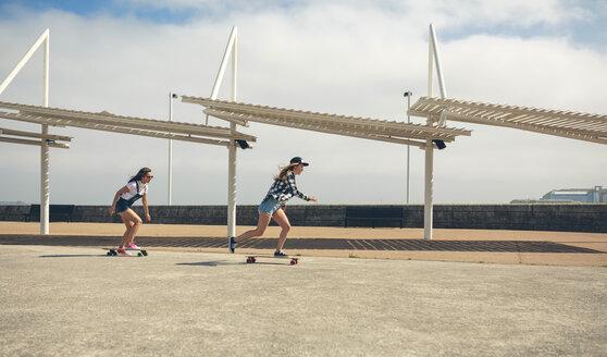 Two young women longboarding on beach promenade - DAPF00776