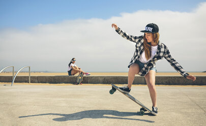 Young woman longboarding while her friend watching her - DAPF00779
