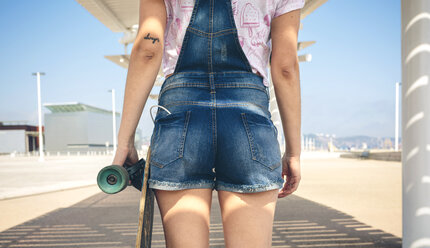 Back view of young woman with longboard on beach promenade, partial view - DAPF00782