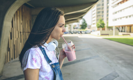 Young woman with headphones drinking strawberry smoothie - DAPF00791