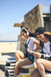 Two happy young women listening music and having fun next to the beach - DAPF00794