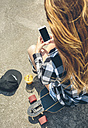 Back view of young woman with long hair looking sitting on longboard looking at smartphone - DAPF00797