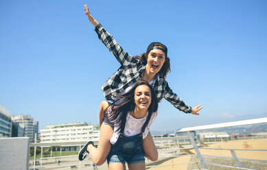 Young woman giving her friend a piggyback ride on roof terrace - DAPF00800