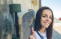 Portrait of smiling young woman with skateboard on her shoulders - DAPF00803