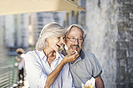Senior couple taking a city break, eating French fries - ZEF14159
