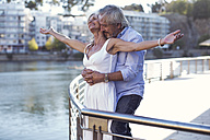 Senior couple taking a city break, embracing at a railing - ZEF14198