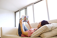Young woman using tablet for video chat at home - HAPF01893