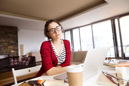 Portrait of pensive freelancer at desk at home - HAPF01902