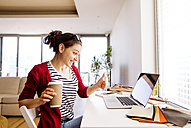 Smiling woman with coffee to go at desk at home - HAPF01908