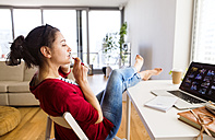Smiling woman on the phone working at desk at home - HAPF01911
