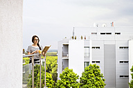 Woman with cup of coffee and personal organizer standing on balcony - HAPF01917