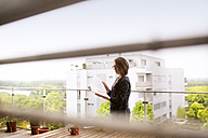 Woman with notebook standiing on balcony - HAPF01920