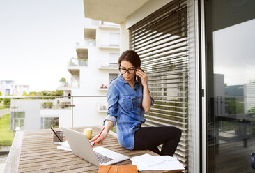 Businesswoman on the phone working on balcony at home - HAPF01926