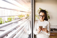 Smiling woman standing at window at home using smartphone - HAPF01935