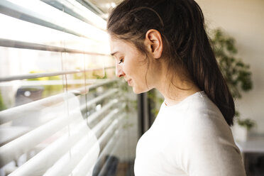 Woman at home looking out of the window - HAPF01941