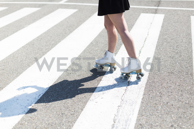 Young woman with roller skates on zebra crossing, partial view - JPF00249 - Javier Pardina/Westend61